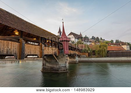 Old medieval covered wooden bridge Lucerne Switzerland with the lights illuminating the inside as dusk falls over the city