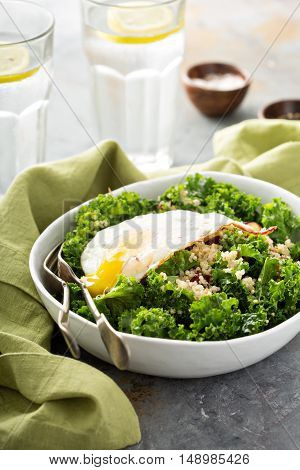 Fresh healthy salad with kale, almond, cranberry and quinoa topped with fried egg