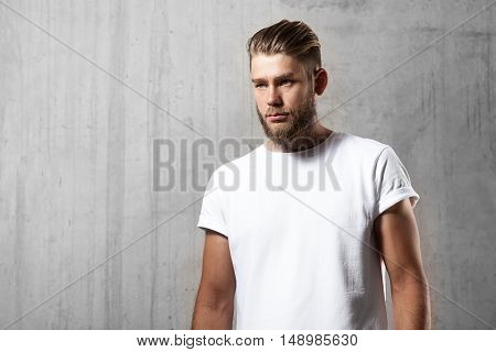 Portrait of bearded man in white t-shirt standing on the cement wall background