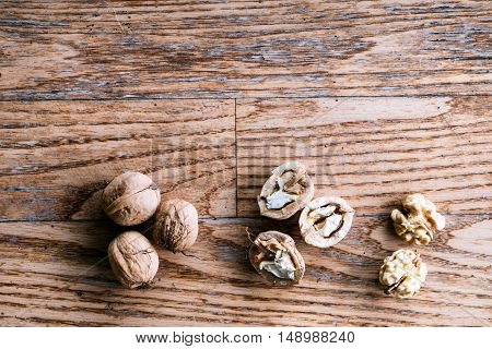 Heap of cracked and whole walnut fruits on wooden background. Studio shot, copy space.