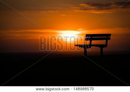 A bench on a hill in Epsom at sunset.