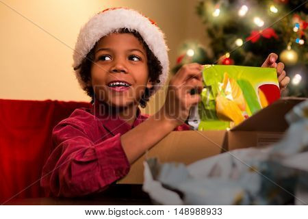 Smiling darkskinned boy unpacks present. Afro kid opens Christmas present. Happiest moment of evening. Holiday for every child.