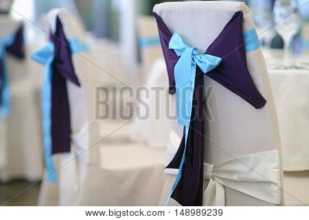 Beautiful fabric bow on the chair. Wedding restaurant for marriage. White decor for bride and groom. Colorful decoration for celebration. Beauty bridal interior