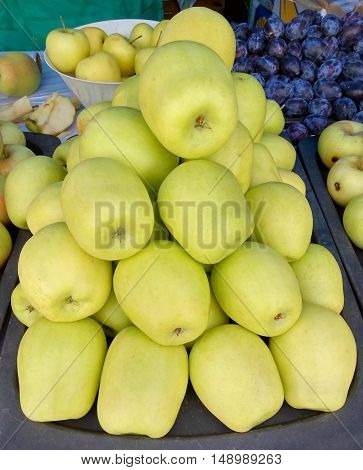 Lots of green-yellow ripe apples at the street market