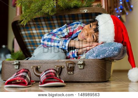 Boy waking up in suitcase. Little Santa's morning smile. Happiest morning of the year. Eager to see the presents.
