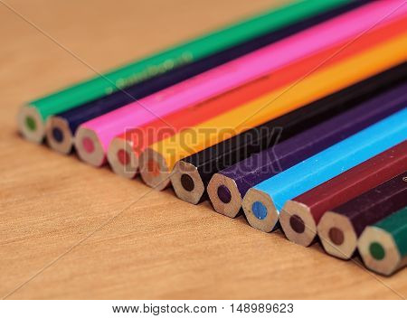 Colored pencils on a wooden board. Macro photo of colored pencils