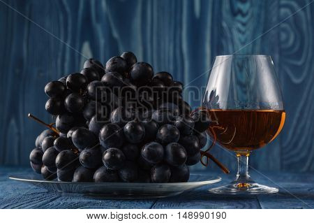 Cognac glass with grape on blue background