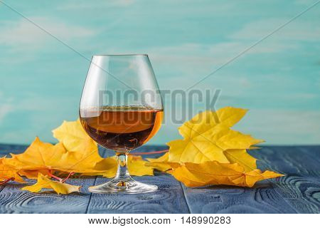 Snifter With Brandy On Blue Table In Bar