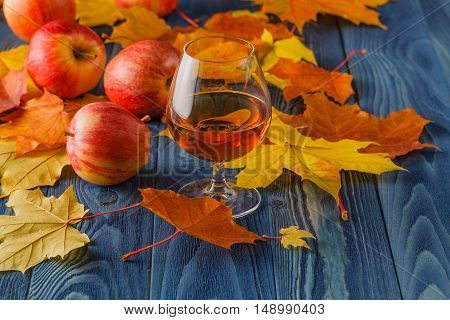 High Angle View Of Glass Of Calvados On Rustic Wooden Table With Apples And Autump Leaves