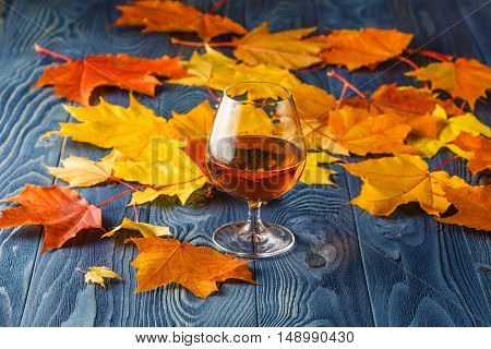 Alcohol drink and autumn leaves on blue