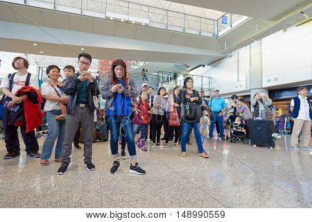 HONG KONG - DECEMBER 24, 2015: Magic perfomance audience at Hong Kong Airport. Hong Kong International Airport is the main airport in Hong Kong.