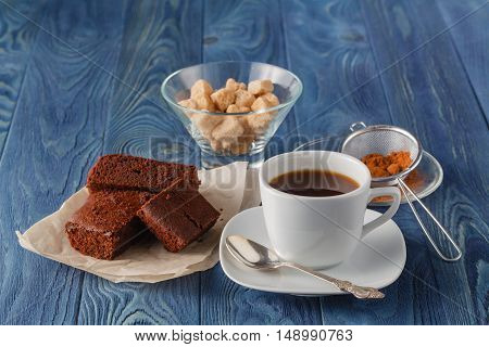 Chocolate Brownie On A White Plate. A Coffee Cup And A Fork On Blue Wooden Table