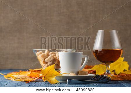 Loving cognac with autumn leaves and coffee
