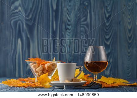 Autumn evening with coffee and cognac on blue
