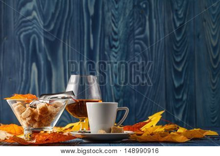 set of coffee and cognac with autumn leaves