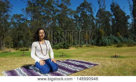 Young latin woman sitting meditating in the park on a blanket fabric