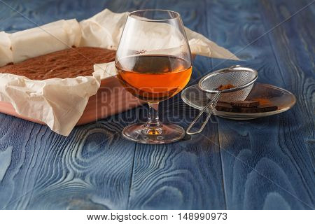 chocolate cake on a baking sheet with glass ow cognac