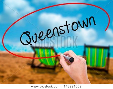 Man Hand Writing Queenstown  With Black Marker On Visual Screen