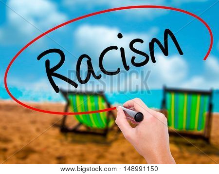 Man Hand Writing Racism With Black Marker On Visual Screen.