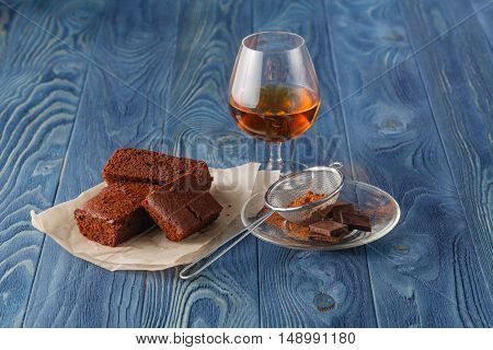 Glass Of Rum On Wooden Tray With Chocolate Brownies In The Background, Selective Focus