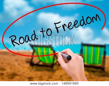 Man Hand Writing Road To Freedom With Black Marker On Visual Screen.