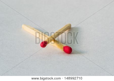 Two matches on white background. Indoor, objects.