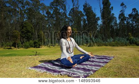 Young latin woman sitting doing yoga in the park on a blanket fabric