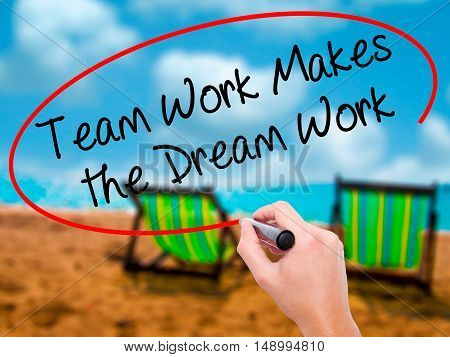 Man Hand Writing Team Work Makes The Dream Work With Black Marker On Visual Screen