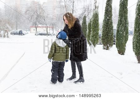 Mom son cleans his nose on a snowy street