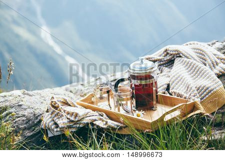Tea on wooden tray over mountains view. Outdoor breakfast in hike.