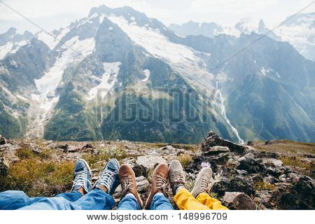 Hikers resting on the mountain, feet over alpine view