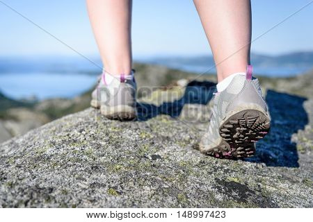 Woman hiking in the mountains - close up of hiking boots