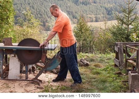 Man cuts wood. Man cutting firewood, preparing for winter. Firewood for heating.