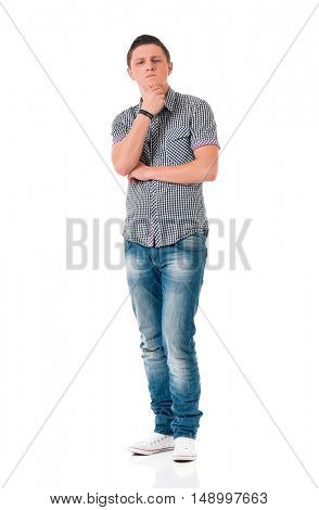 Young man looking thoughtful while holding his head. Guy standing full length portrait, isolated on white background.