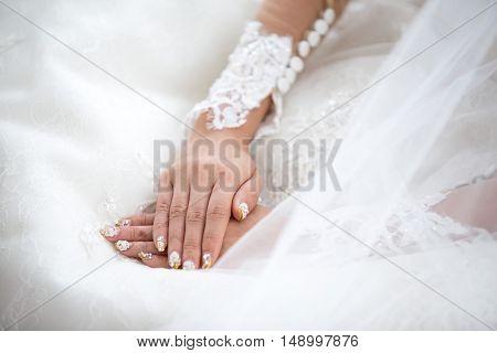 Tender beautiful bride's hands on elegant white wedding dress closeup.