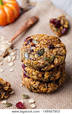 Oat cookies with cranberries and maple glaze on a rustic textile background.