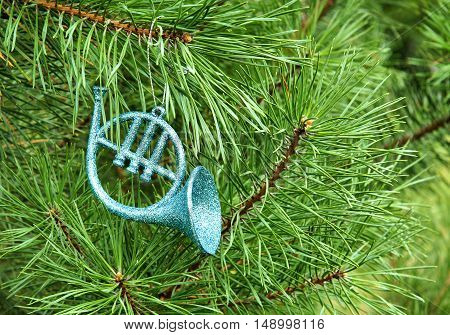 Toy french horn on spruce branch is a Christmas decoration