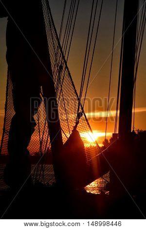 Zonsopkomst met masten en touwen in de haven van Amsterdam