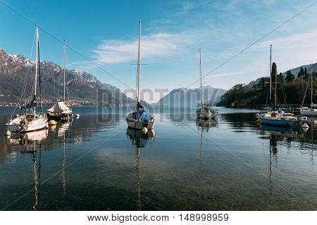 Magnificent view of the Como lake with Alps mountains in the background and boats in the bay