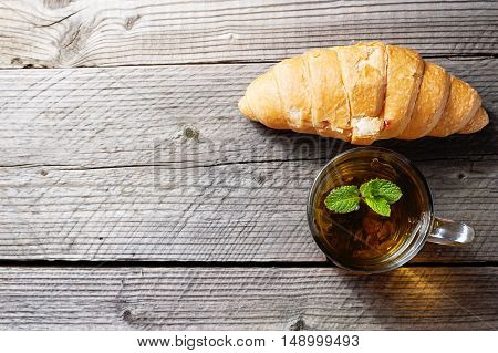 Cup of tea and croissants on a wooden background top view, copy space.