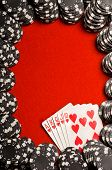 Black poker chips and a Royal Flush on red felt