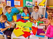 Group of school children are making something out of colored paper on table in primary school. Child poster