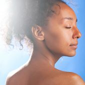 stock photo of black woman spa  - sunny beautiful mulatto woman with closed eyes on sky background - JPG