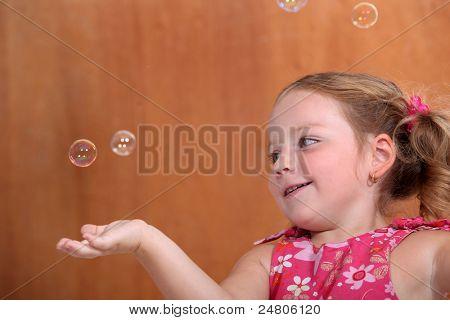 Kleines Mädchen fangen Blasen