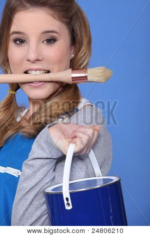 portrait of cute blonde painter holding brush between teeth against blue background