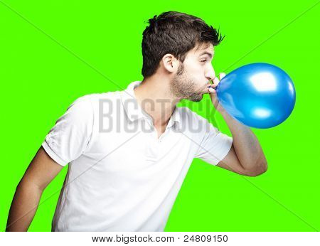 portrait of young man blowing a balloon over removable chroma key background