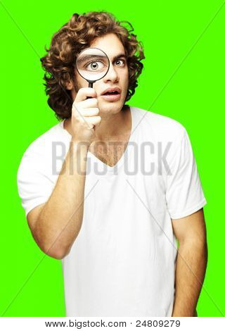 portrait of young man looking through a magnifying glass against a removable chroma key background