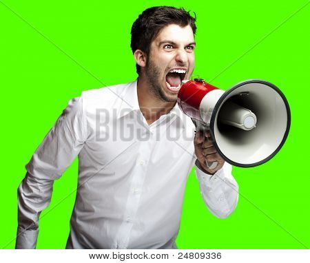 portrait of young man shouting with megaphone over removable chroma key background