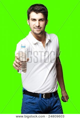 portrait of a healthy young man offering water bottle over removable chroma key background