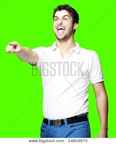 portrait of young man pointing and laughing over removable chroma key background